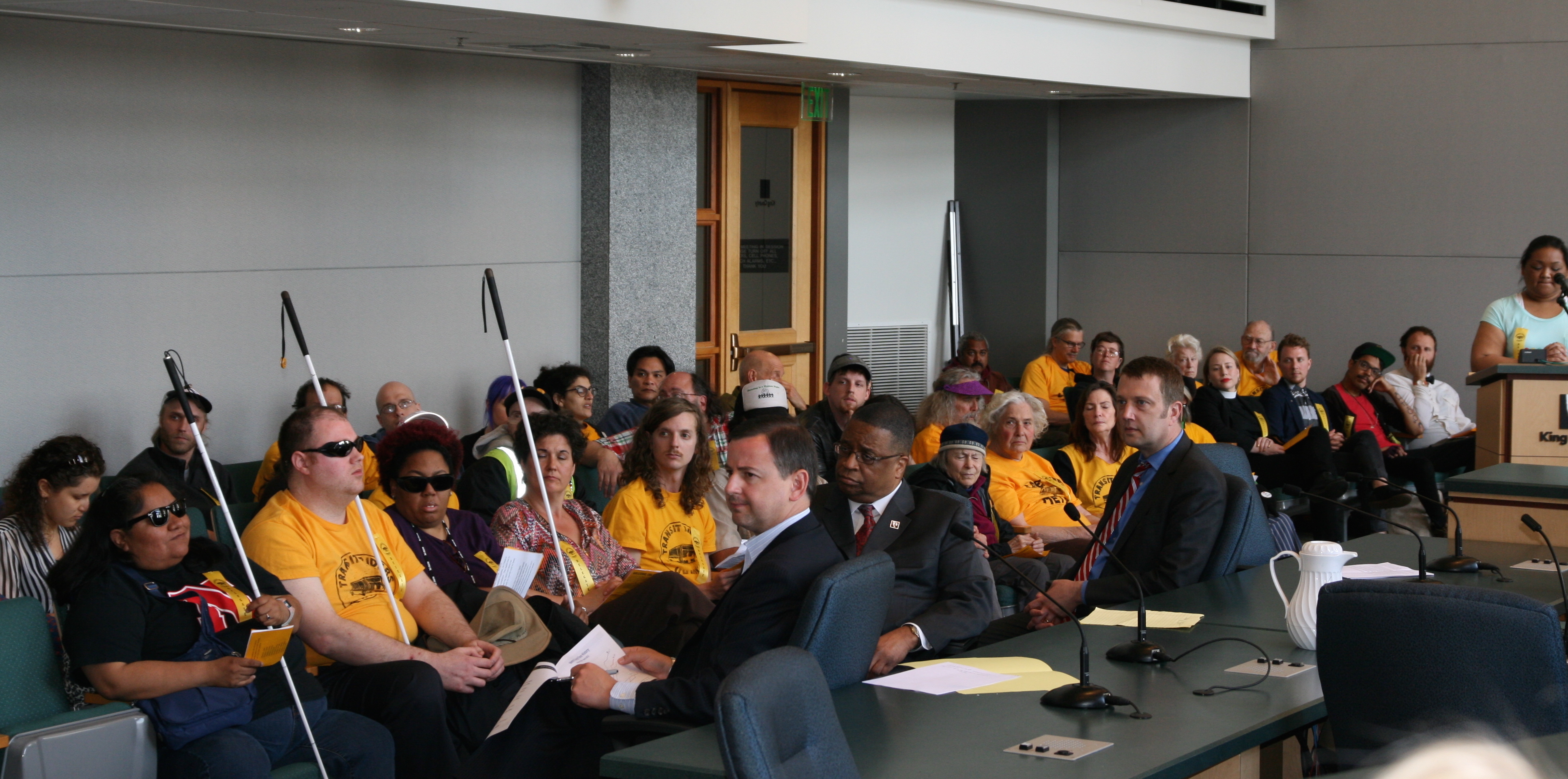 The Councilmembers listen to a delegate testifying to the need for lower transit fares.